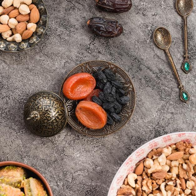 Droge abrikoos en zwarte rozijn op metaalplaat met noten op concrete achtergrond Gratis Foto