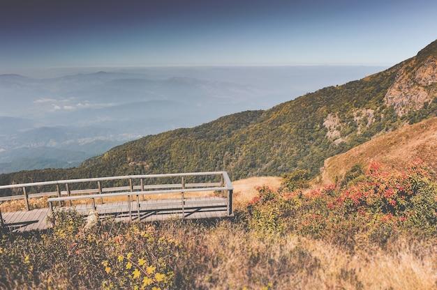 Droge bergweide, mistwolklandschap en houten brug. Premium Foto