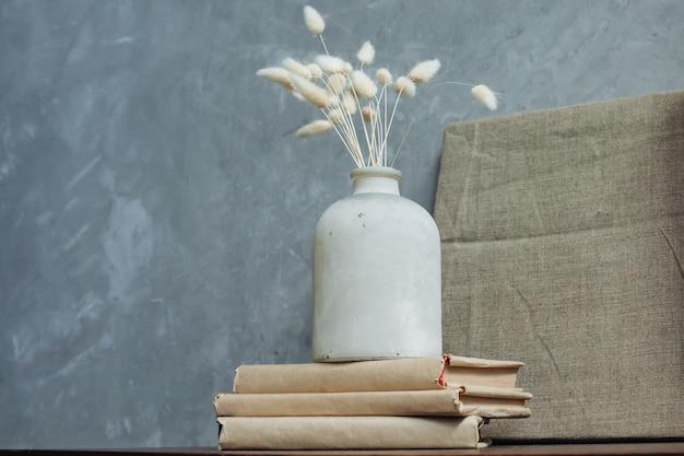 Droge bloemen in een oude vaas op de achtergrond van een linnen schilderij. ruimte voor tekst. Premium Foto