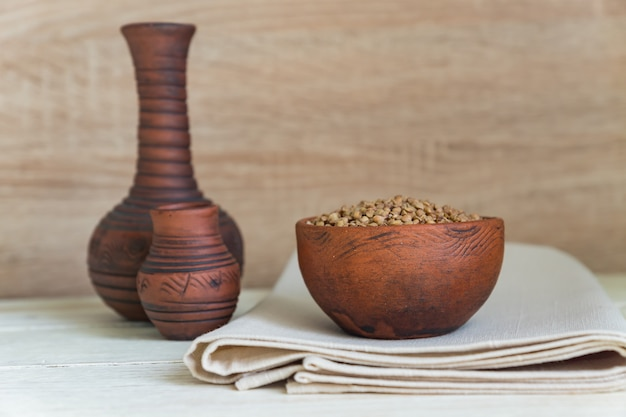 Droge boekweit in bruine kleikom op houten lijst. glutenvrij graan voor een gezond dieet Premium Foto