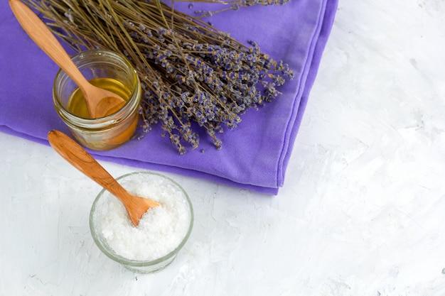 Droge de lavendelbloemen van het hoogste uitzicht, honingskruik, overzees zout, kuuroord dat op witte sjofele concrete achtergrond wordt geplaatst Premium Foto