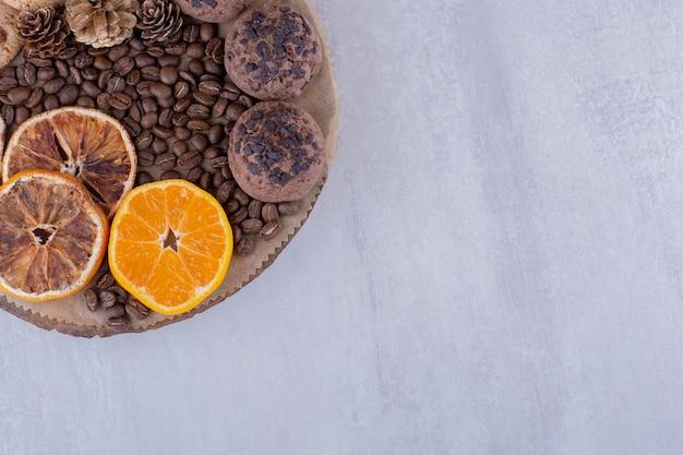 Droge en sappige stukjes sinaasappel, koffiebonen, dennenappels en koekjes op een bord op witte achtergrond. Gratis Foto
