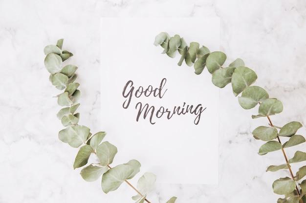 Droge eucalyptustakken over de goedemorgen met de hand geschreven op witboek tegen geweven achtergrond Gratis Foto
