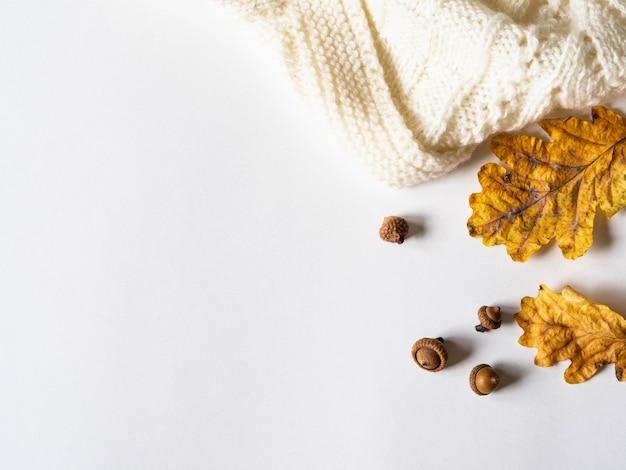 Droge gele eikenbladeren en eikels en warme gebreide lichte plaid. de herfstsamenstelling op een witte achtergrond Premium Foto