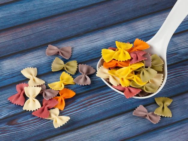 Droge kleurrijke italiaanse deegwaren farfalle of bogen met lepel op donkerblauwe houten achtergrond. met kopie ruimte Premium Foto
