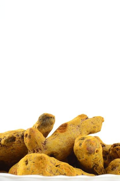 Droge kurkuma wortels of blaft geïsoleerd op een wit oppervlak Premium Foto