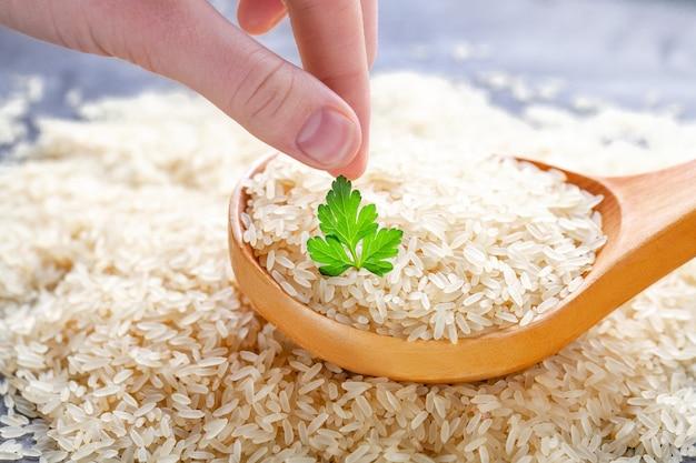 Droge lange rijst in grote houten lepel met verse groene peterselie. Premium Foto