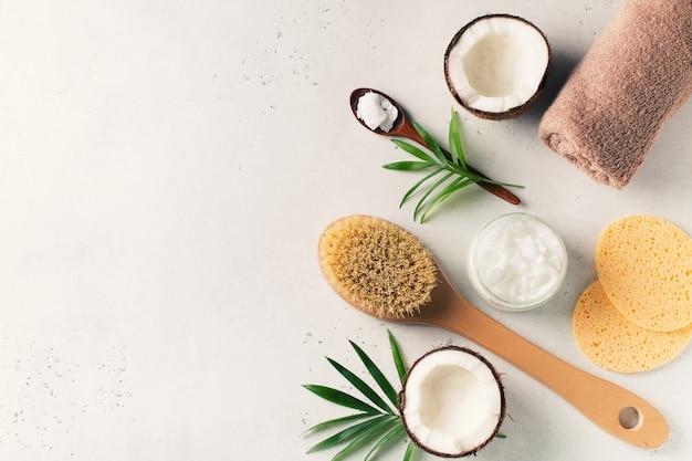 Droge massageborstel met kokosnotenolie, het concept van gezondheidsgezondheid met toebehoren op witte achtergrond Premium Foto