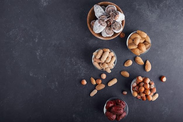 Droge noten en fruit in een glazen beker op een grijze achtergrond, bovenaanzicht. Gratis Foto