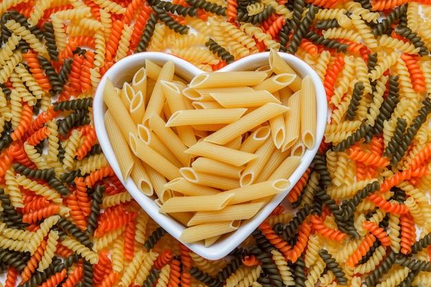 Droge penne pasta in een hartvormige plaat plat lag op een gekleurde fusilli tafel Gratis Foto