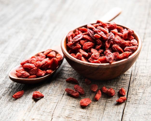 Droge rode gojibessen voor een gezond dieet op een oude houten ondergrond Premium Foto