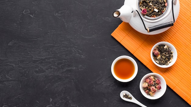 Droge theedelen in ceramische kom met theepot op placemat over zwarte oppervlakte Gratis Foto
