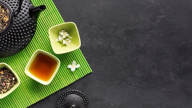 Droge theekruiden en kruidenthee met witte jasmijnbloem op groene placemat op zwarte achtergrond Gratis Foto