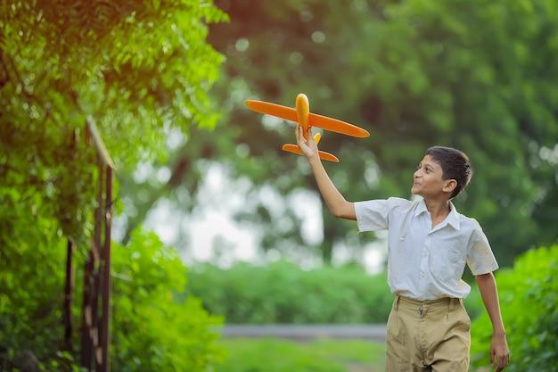 Dromen van vluchten! indiase kind spelen met speelgoed vliegtuig Premium Foto
