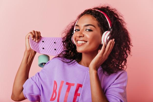 Dromerig afrikaans meisje luisteren muziek in grote koptelefoon. aantrekkelijk zwart vrouwelijk model poseren met longboard op pastel lachen. Gratis Foto