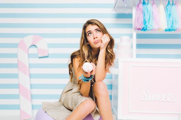 Dromerig donkerbruin meisje betwijfelt of het de moeite waard is om ijs te eten dat op een gestreepte muur ligt te koelen. portret van doordachte jonge vrouw zit naast snoepwinkel en lekker dessert in de hand te houden. Gratis Foto