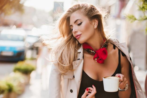 Dromerig gebruind meisje in lichtbruin jasje met gesloten ogen aan iets denken en genieten van een goede dag. schattige vrouw met kopje thee tijd buiten doorbrengen in de ochtend. Gratis Foto