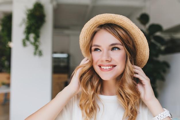 Dromerig lachend meisje met bleke huid opzoeken en mooie krullen aanraken Gratis Foto