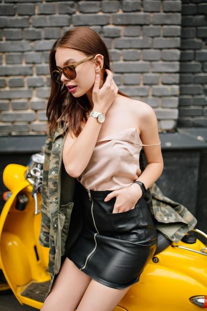 Dromerig meisje met sluik bruin haar in polshorloge wegkijken zittend op gele bromfiets Gratis Foto