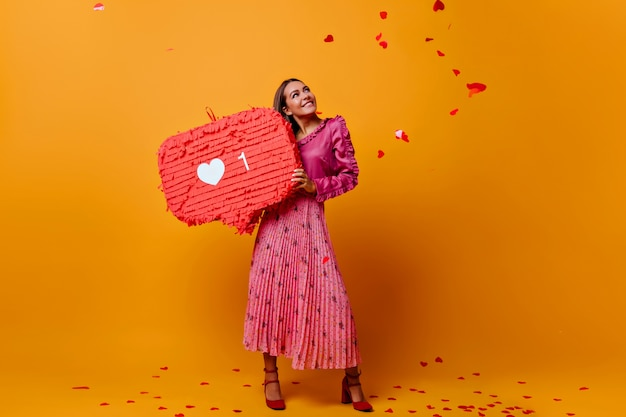 Dromerig romantisch meisje in een goed humeur tijdens fotoshoot met grote like in haar handen. model in modieuze blouse met franje Gratis Foto