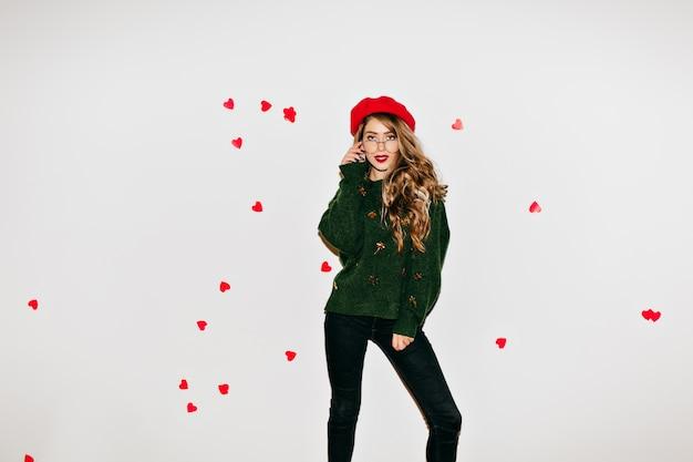 Dromerige dame in baret staande in zelfverzekerde pose tijdens het poseren in valentijnsdag Gratis Foto