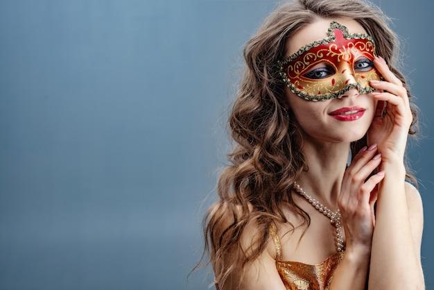 Dromerige donkerbruine vrouw in een kleurrijk carnaval-masker op een blauwe achtergrond Premium Foto