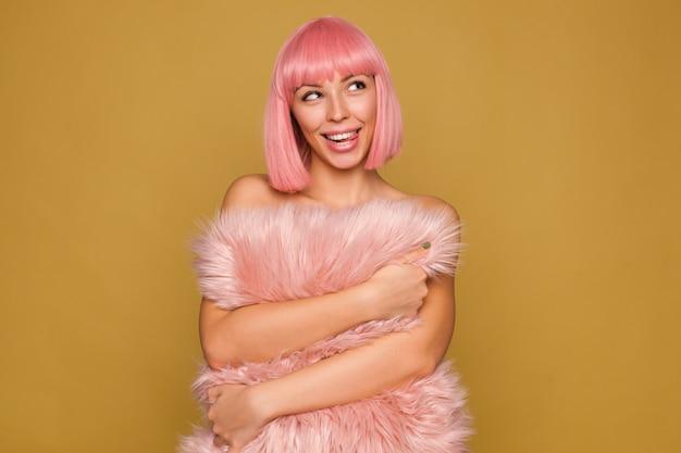 Dromerige jonge, mooie vrolijke vrouw met roze bobkapsel dat haar tong uitsteekt terwijl ze gelukkig opzij kijkt, een roze harig kussen omhelst terwijl ze poseert voor de mosterdmuur Gratis Foto