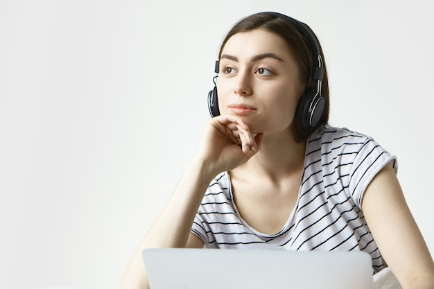 Dromerige jonge vrouw in vrijetijdskleding thuis ontspannen, luisteren naar muziek met behulp van online applicatie op laptop Gratis Foto