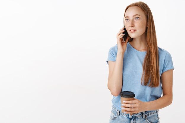 Dromerige, knappe vrouw met een ontspannen blik met een papieren kopje koffie terwijl ze telefoneert Gratis Foto
