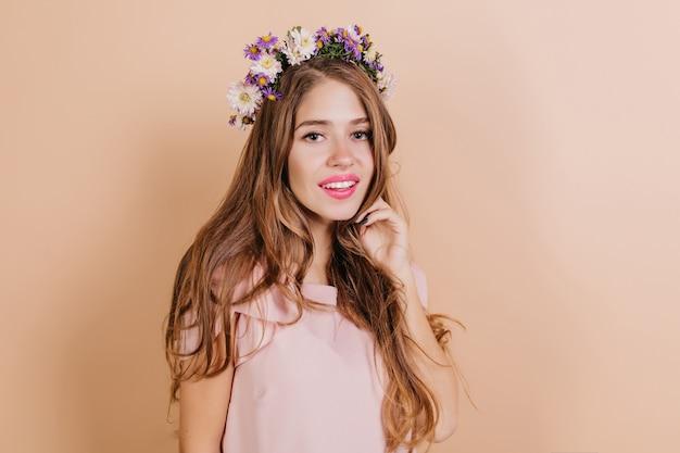 Dromerige langharige brunette vrouw met paarse bloemen in haar glimlachen naar de camera Gratis Foto