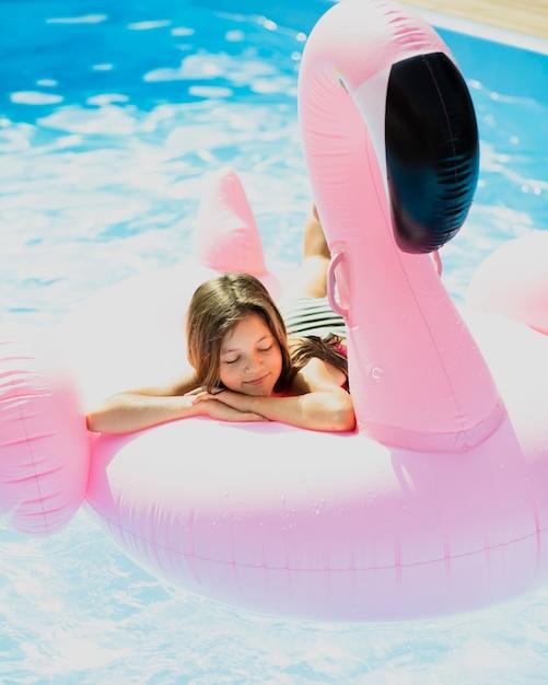 Dromerige meisjeszitting op een flamingofloatie Gratis Foto