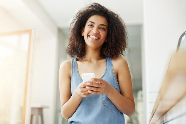 Dromerige mooie afrikaanse vrouw die het denken het dromen de zitting van de holdingstelefoon in koffie glimlachen. Gratis Foto