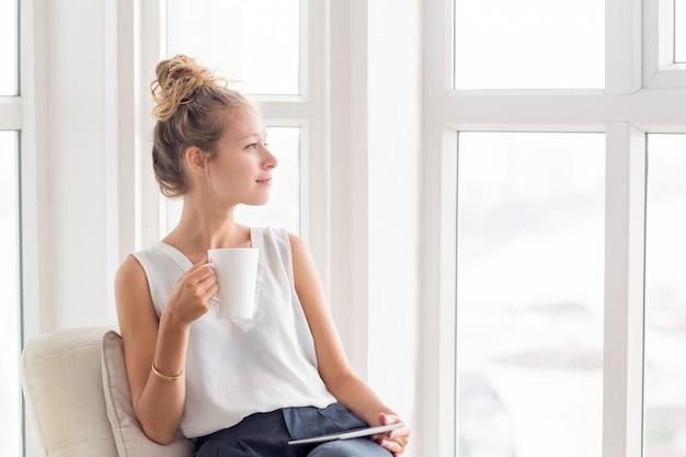 Dromerige mooie vrouw met thee en tablet op loggia Gratis Foto