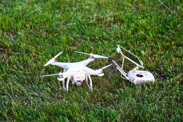 Drone quad copter met hoge resolutie digitale camera en de afstandsbediening pad met smartphone op gras Premium Foto