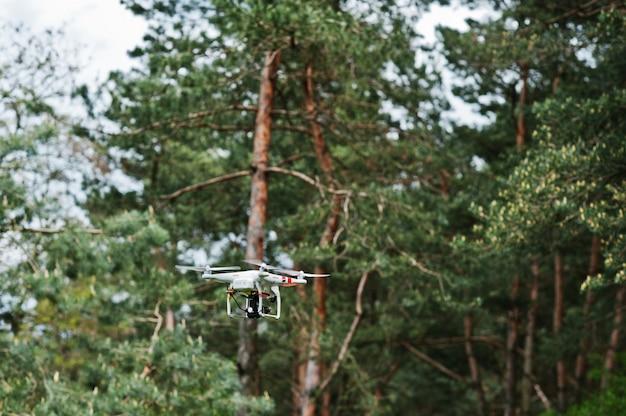 Drone quad copter met hoge resolutie digitale camera tegen dennenbos. Premium Foto