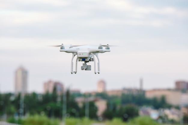 Drone quad copter met hoge resolutie digitale camera vliegen zwevend boven de stad Premium Foto