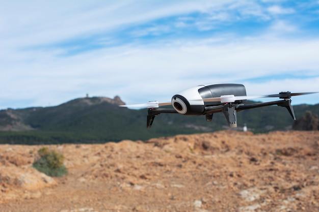 Drone vliegt over het veld, met aarde, bergen en blauwe lucht rond. Premium Foto