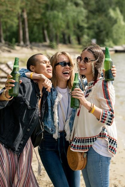 Dronken blond-haired meisje omhelst vrienden en lachen terwijl ze bier drinkt met hen op het strand Premium Foto