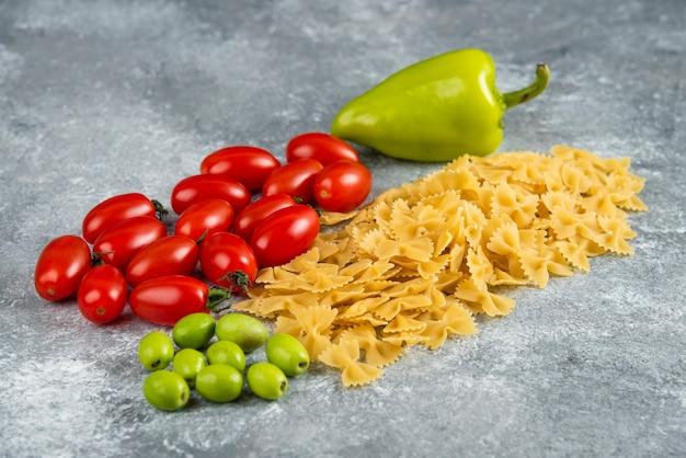 Droog farfalle en groenten op marmer. Gratis Foto