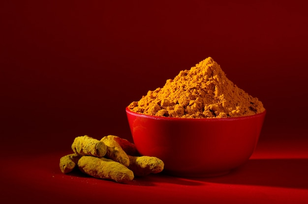 Droog kurkumapoeder en wortels of blaft in rode kom op rood oppervlak Premium Foto