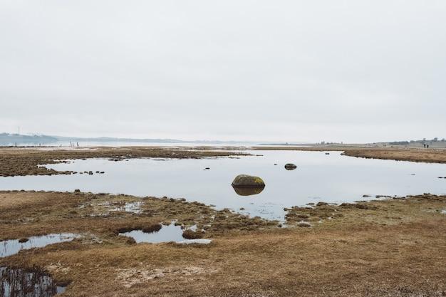 Droog landschap vol water onder een bewolkte hemel Gratis Foto