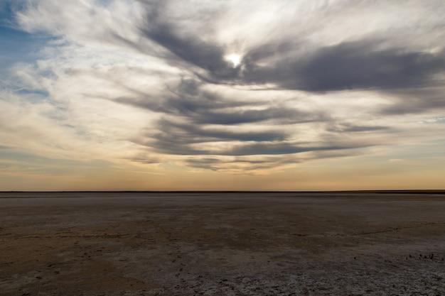 Droog meer, woestijn in kazachstan, zout meer, droog meer in de steppe en bewolkte hemel Premium Foto