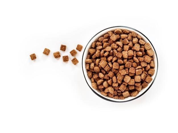 Droog voedsel voor huisdieren in een witte ceramische kom die op witte oppervlakte wordt geïsoleerd Premium Foto