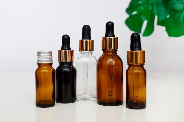 Dropper glazen flessen bespotten. cosmetische pipet op witte achtergrond met tropisch verlof. Premium Foto