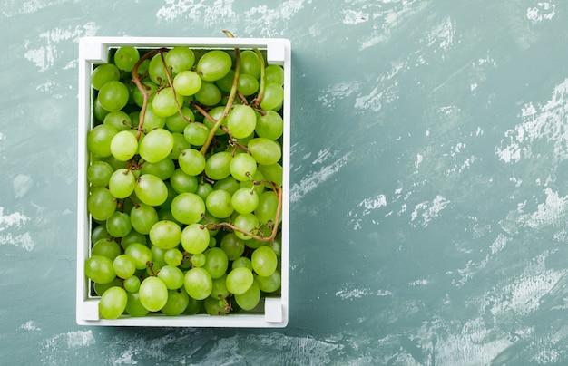 Druiven in een houten doos bovenaanzicht op een grungy pleister achtergrond Gratis Foto