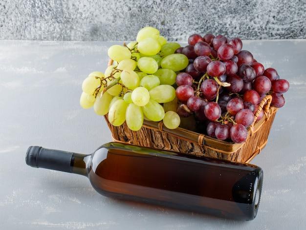 Druiven in een mand met drankfles hoge hoekmening over gips en grungy Gratis Foto