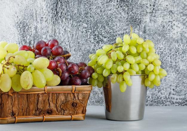 Druiven in mini-emmer en mand zijaanzicht op gips en grungy grijs Gratis Foto