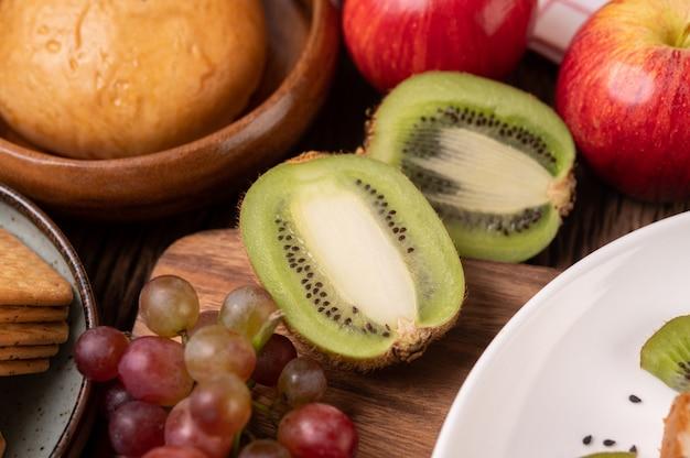 Druiven, kiwi, appels en brood op tafel Gratis Foto