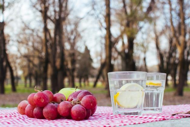Druiven naast glazen met water en citroen Gratis Foto