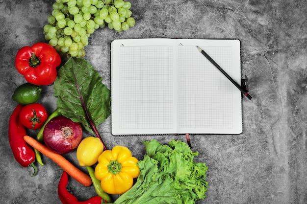 Druiven, paprika, greens, citroen, tomaat en leeg notitieboekje op marmeren achtergrond. Gratis Foto